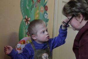 Ваня дотягивается до лица и трогает очки воспитателя